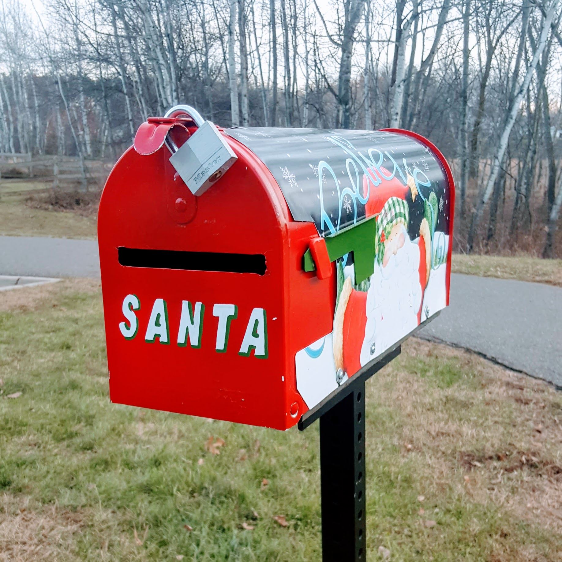 Bright red mailbox decorated with Santa's picture and name