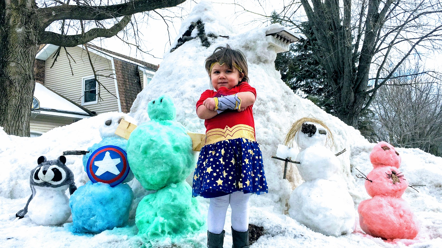 Child Dressed as Wonder Woman Poses with Hero Snowmen