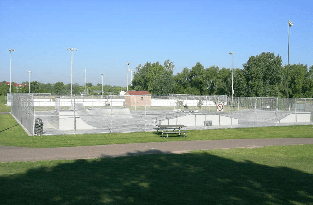 Fenced in Walton Park skate park with paved surface and ramps