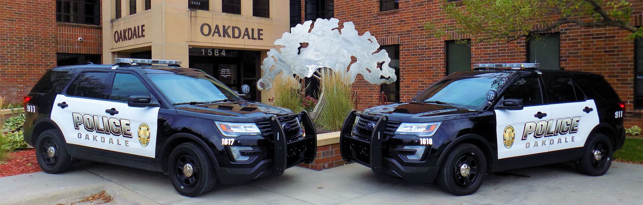 Two Oakdale police cars parked in front of city hall
